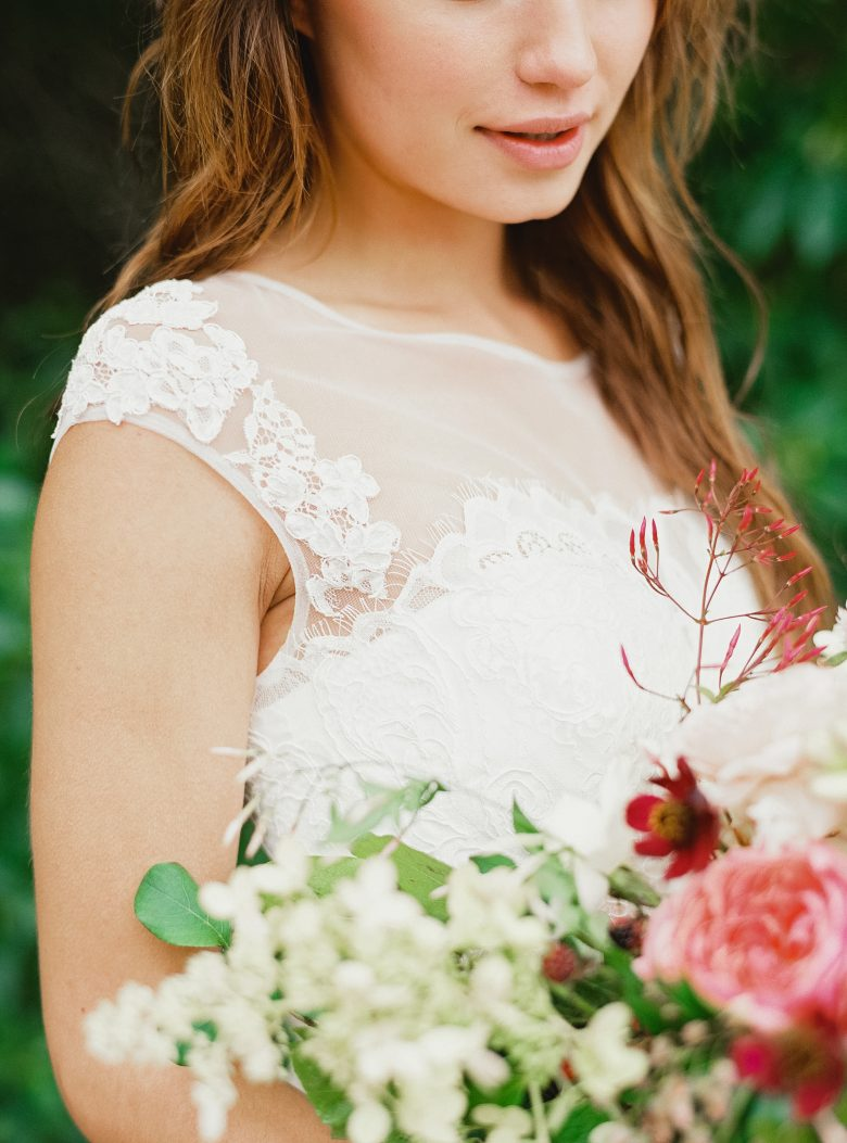 close up of white lace shirt on a brunette and light flowers