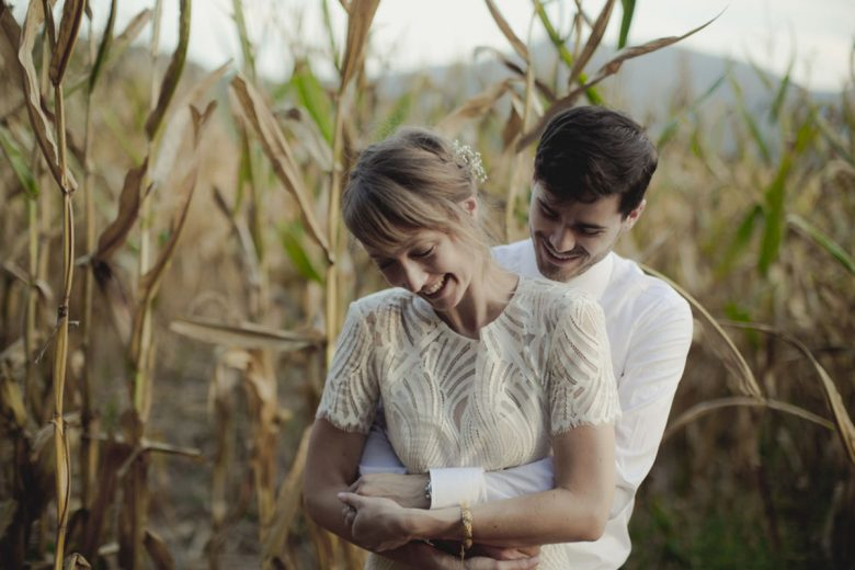 bride and groom embracing in a cornfield