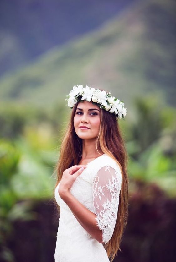 a beautiful bride looks at the camera wearing a flower crown full of white flowers and the jungle mountains behind her in the distance