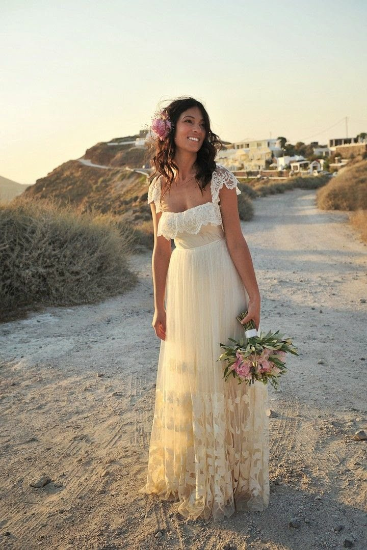 a bride stands in the middle of a dirt road in the mountains with the setting sun bathing her in beautiful orange light