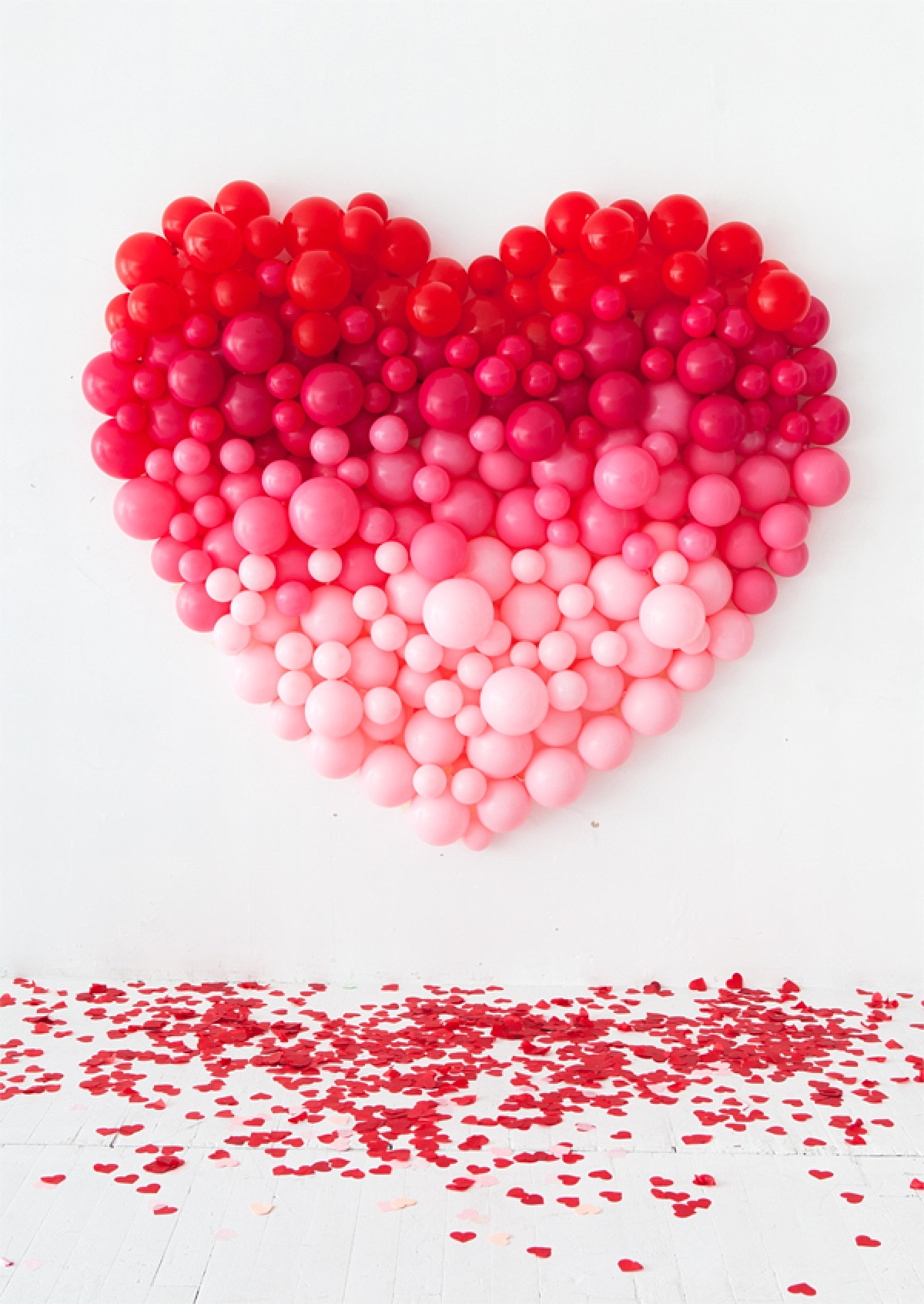 Ombre heart baloon sculpture hanging on white wall with cutout red and pink hearts scattered on the ground below