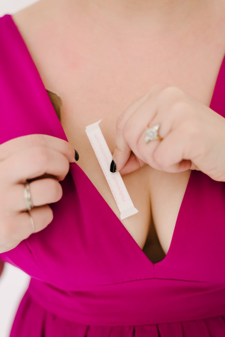 closeup of fashion tape being put on neckline of pink dress