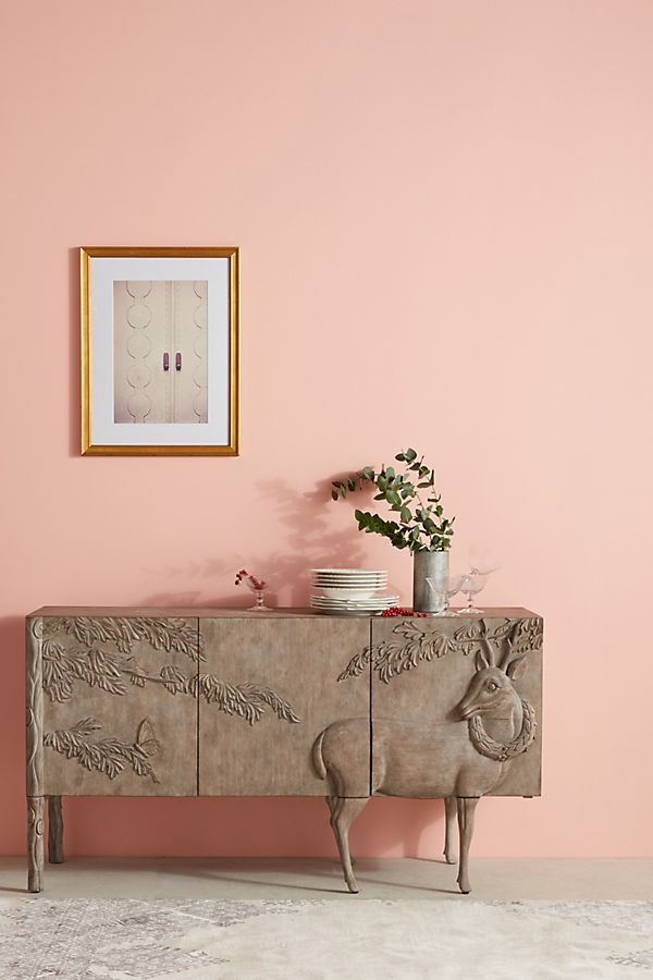 Carved buffet with deer image in a pink room