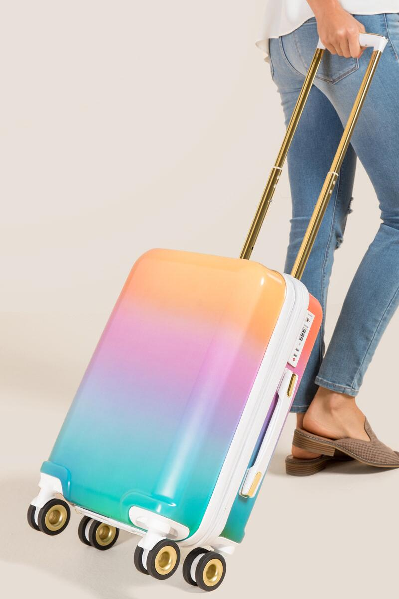 A woman pulling a pastel rainbow carry on luggage