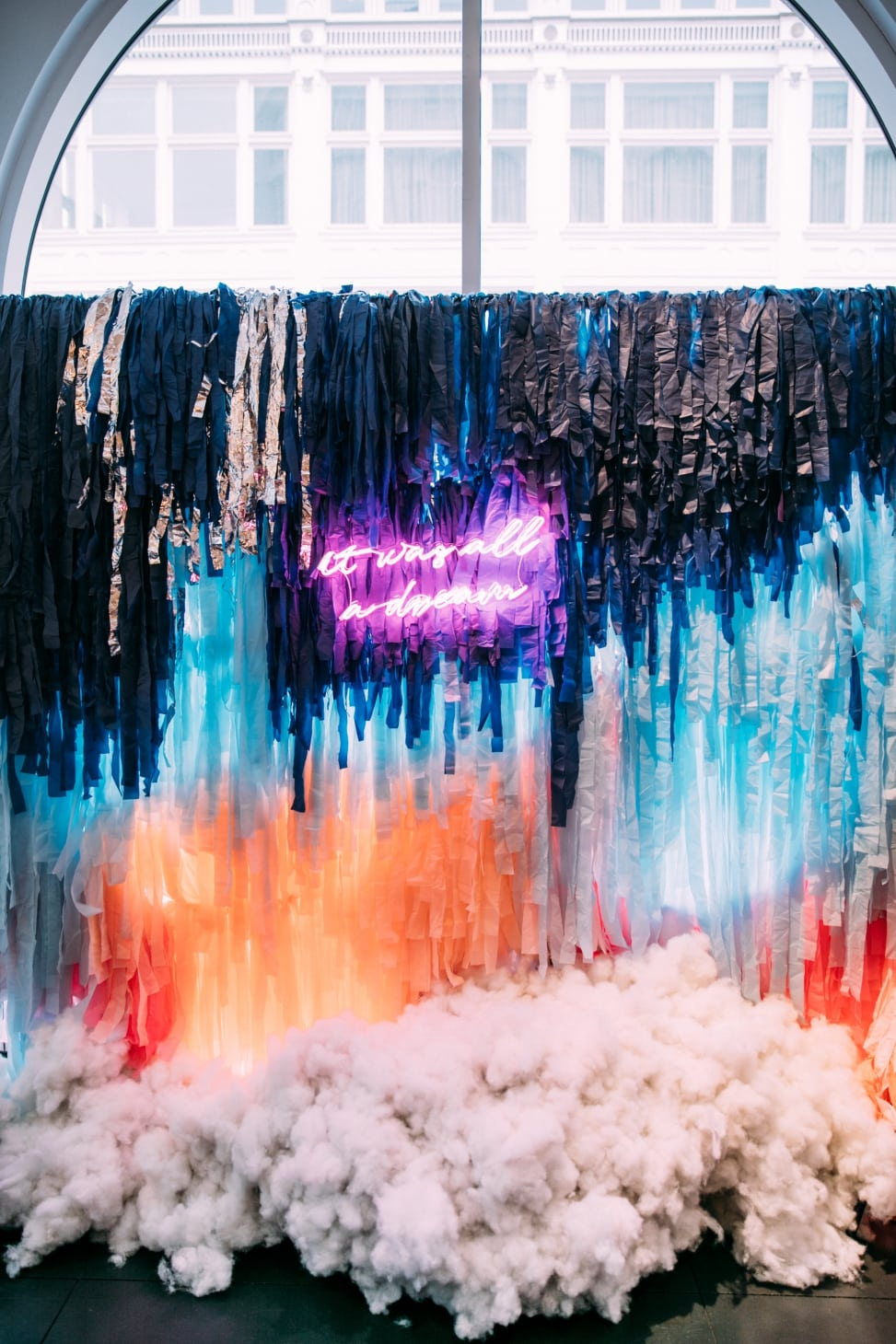 "A colorful neon colored backdrop with cloud below and neon sign that reads ""it was all a dream"" at the crate and barrel san francisco private registry event with a practical wedding"