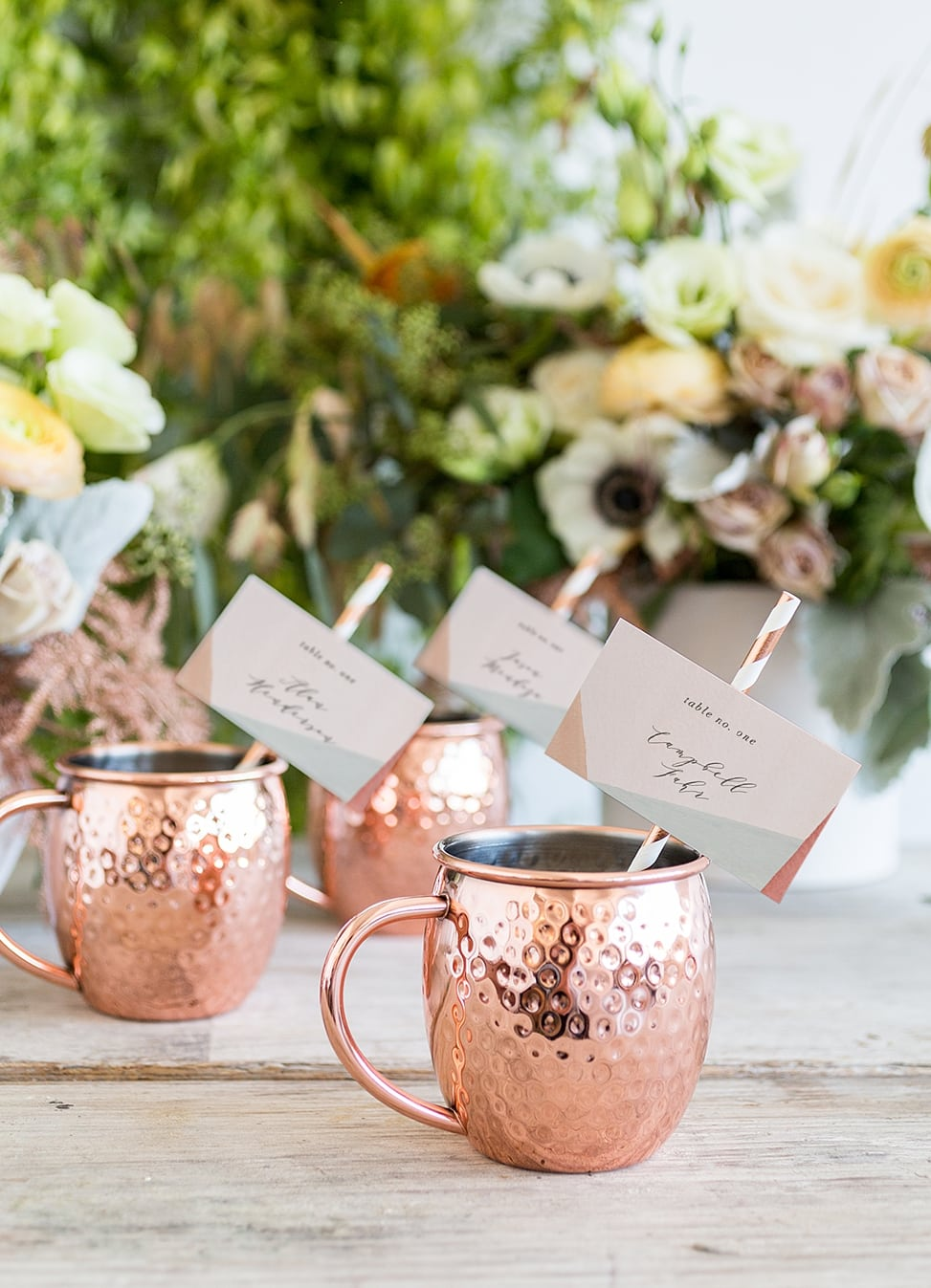 moscow mule cups with paper straws and name cards from minted weddings