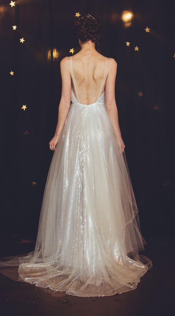 Back of woman in winter wedding colors: a sparkling dress of translucent sequins